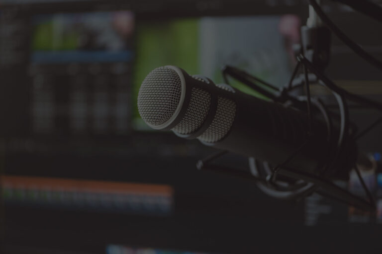 A broadcasting microphone in front of a laptop screen