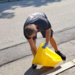Happy Valley team member bending to pick up trash at Gloucester