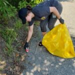 Happy Valley team member picking up trash from bushes